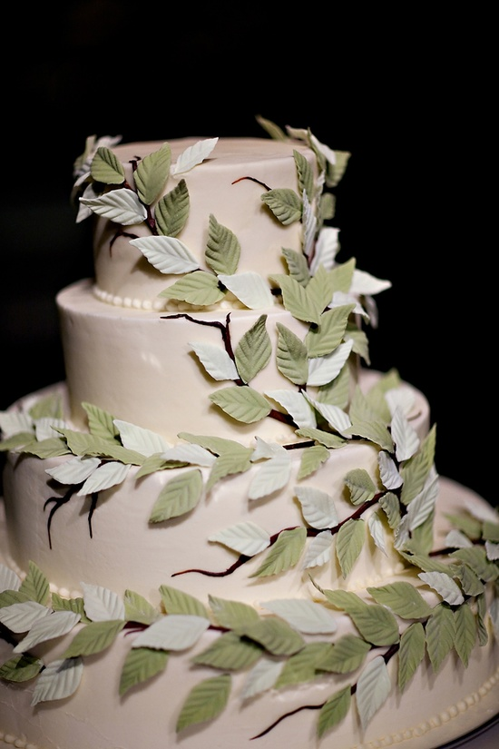 Elegant ivory wedding cake adorned with sugar leafs