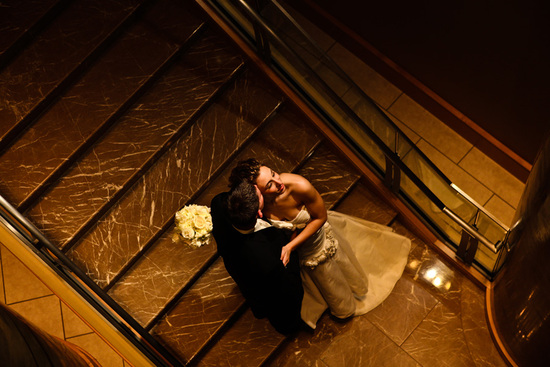 Bride and groom kiss on stairway of wedding venue
