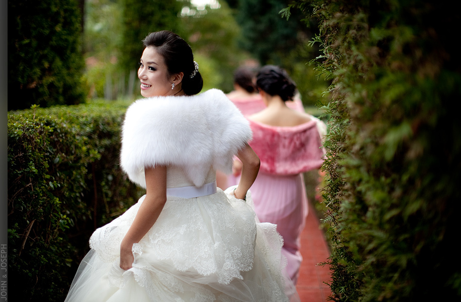 Bride wears fur bridal bolero over lace wedding dress