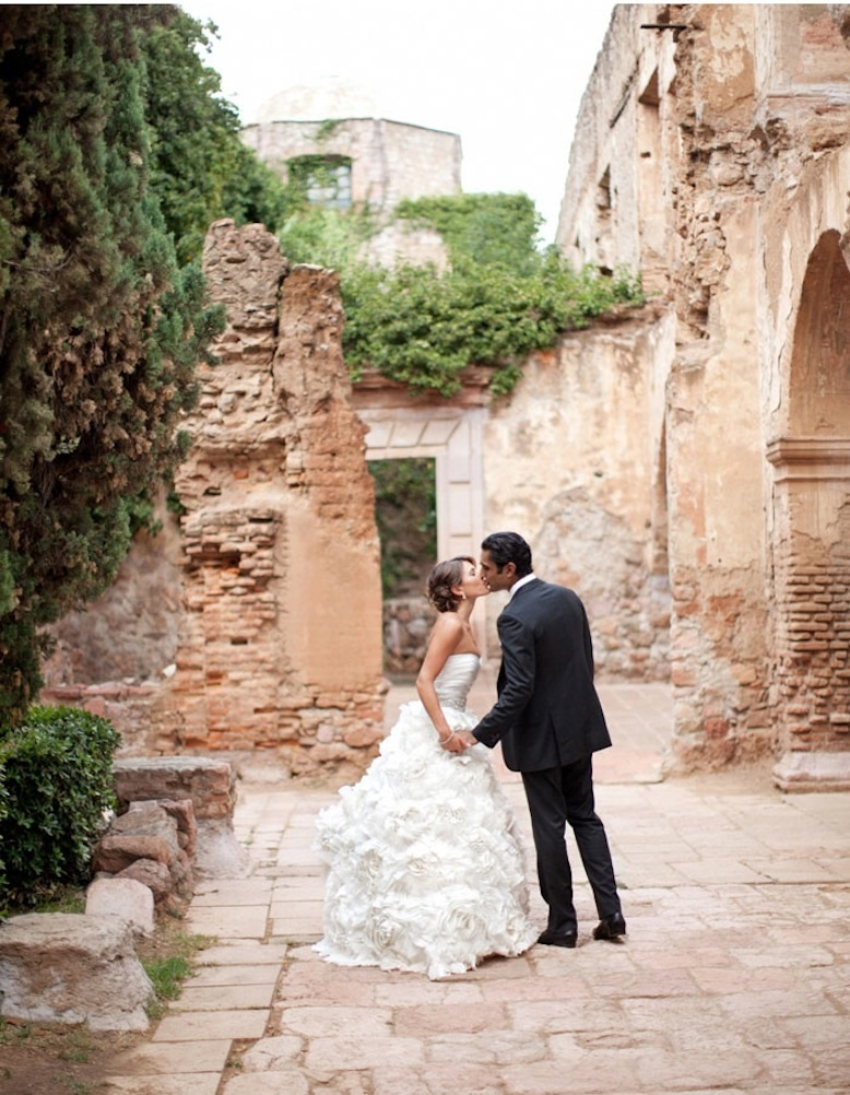 bride and groom kiss outside ruins in Mexico
