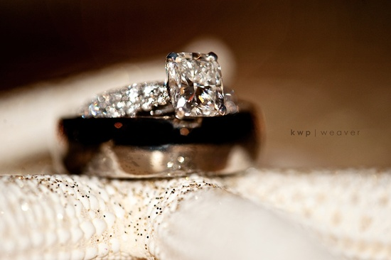 Artistic photo of bride's engagement ring, groom's wedding band
