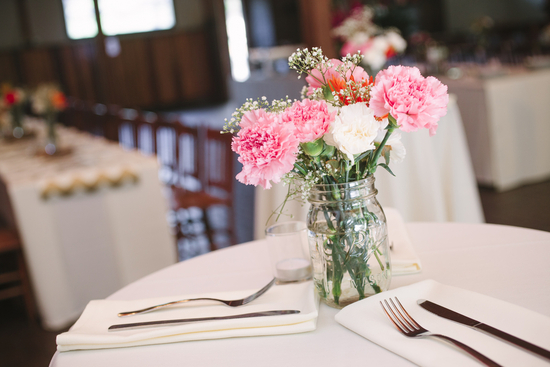 pink and white carnations in mason jars for wedding reception centerpieces