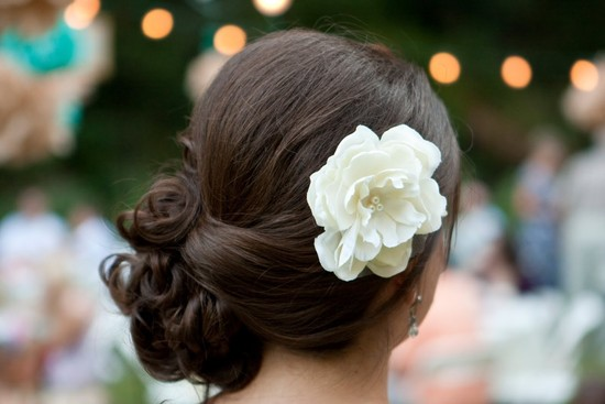 Side chignon wedding hairstyle finished with a simple ivory flower