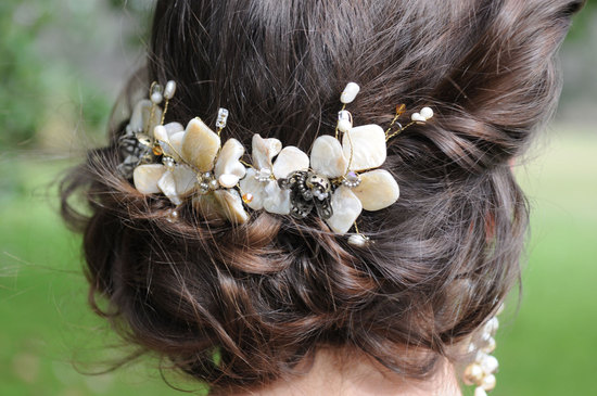 romantic low wedding updo with pearl floral accent clip