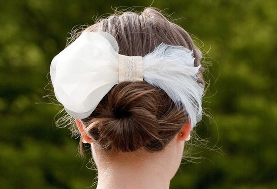 Simple twisted bun wedding updo with feather and organza hair clip