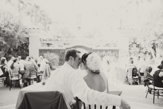 Happy bride and groom kiss at outdoor wedding reception