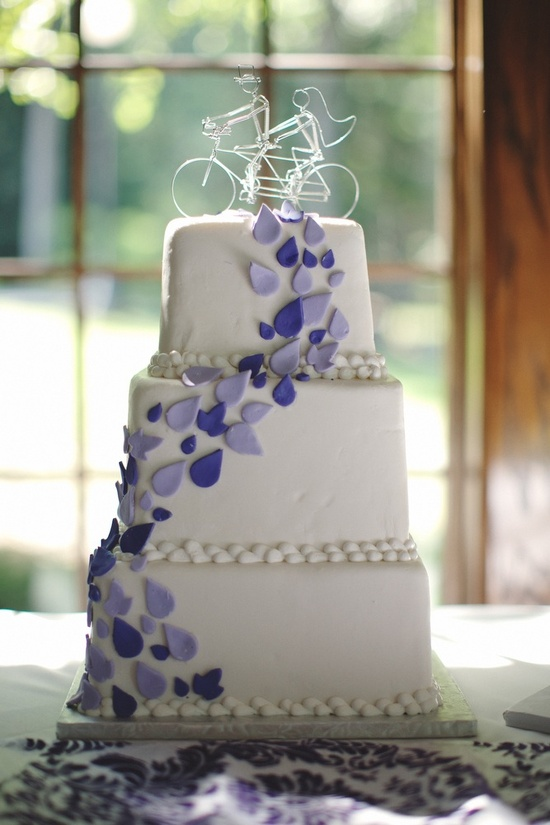 White wedding cake with purple wedding flowers