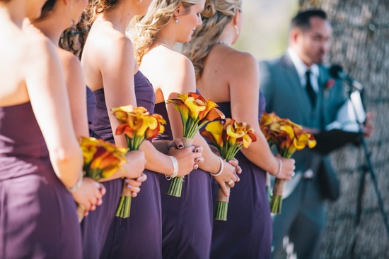 bridesmaid escorted by two groomsmen down outdoor ceremony aisle