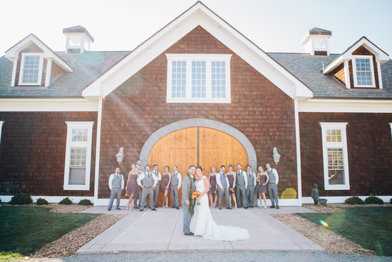 bride and groom pose with wedding party in back