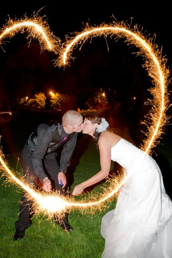Bride and groom kiss under sparklers heart