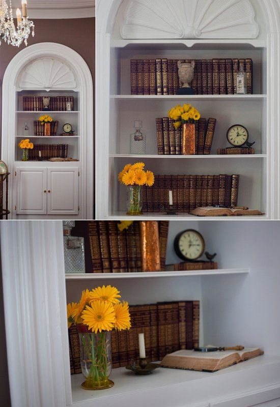 Vintage bookshelf adorned with yellow wedding flowers, metallic accents