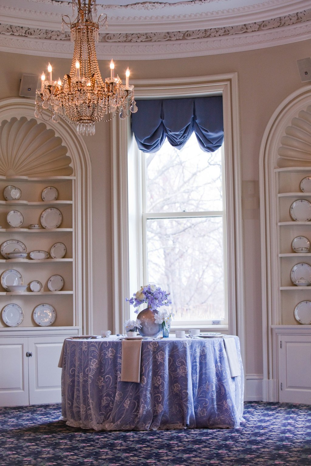 Elegant wedding reception venue with sparkling chandelier, blue, lilac ivory wedding flowers
