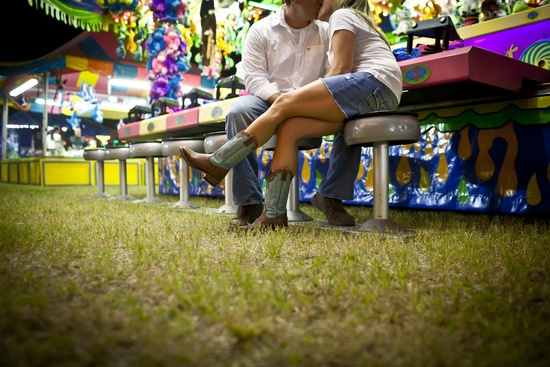 Bride and groom take engagement photos at carnival
