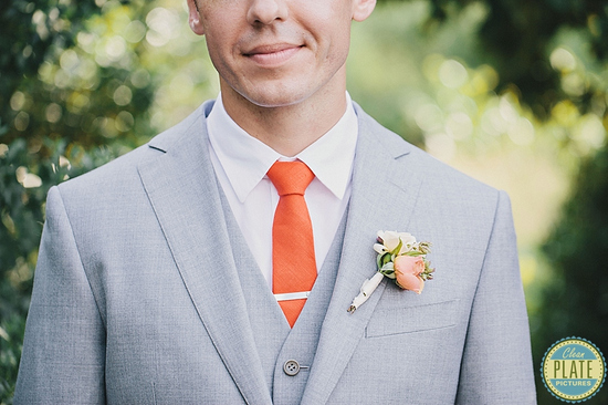 groom wears three piece light gray suit with bright orange tie