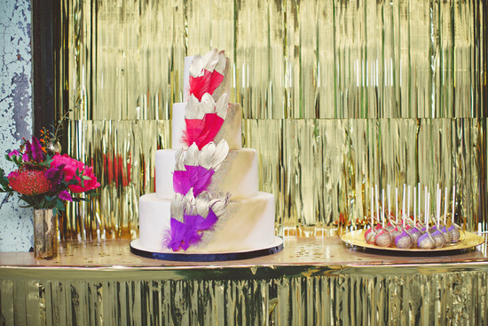 Gold foil dipped feathers adorn classic wedding cake