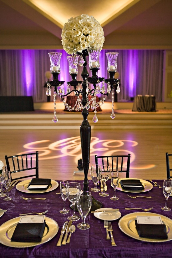 Ivory roses atop black candelabra draped with crystals at chic wedding reception