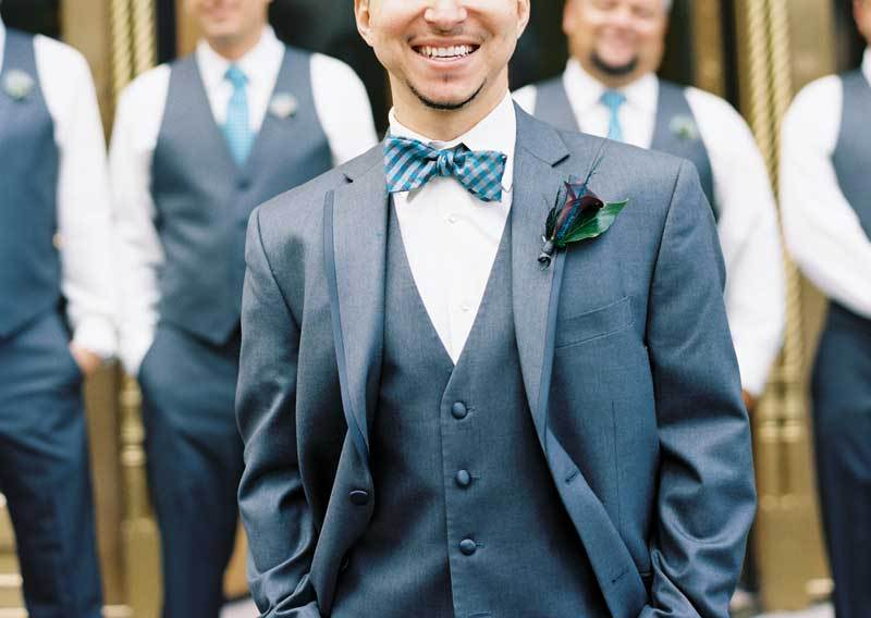 suit in charcoal gray with teal and gray bow tie