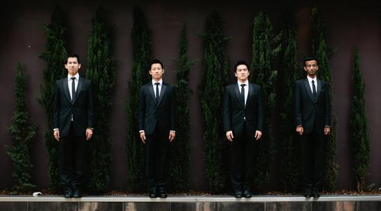 photo of classic groom and groomsmen in black tuxedos