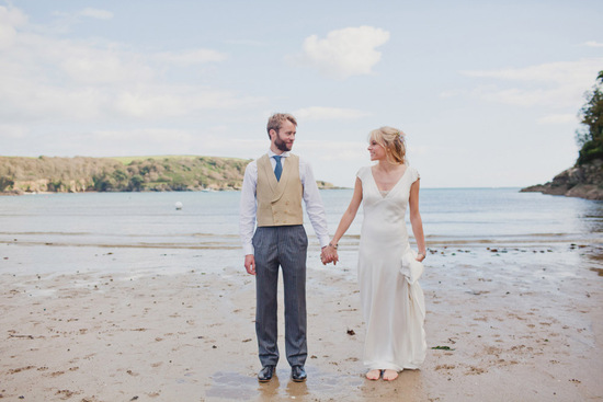 Groom wears khaki vest and striped navy pants for seaside wedding