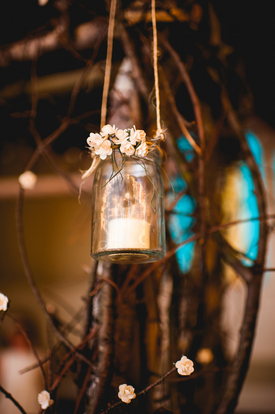 Mason jars hanging from branches for wedding reception decor