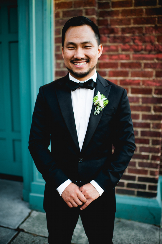 Handsome groom wears black three piece suit with bow tie