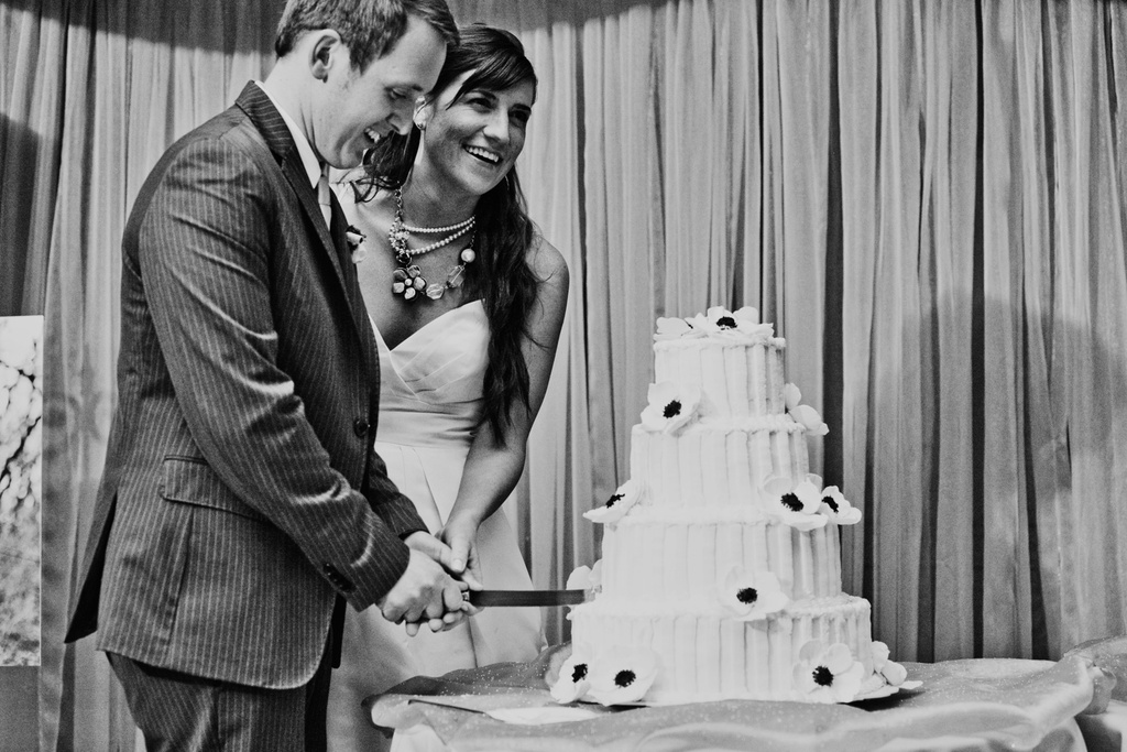 Bride and groom cut ivory wedding cake at wedding reception in Kansas City