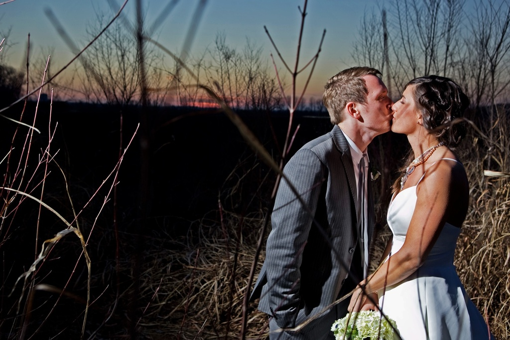 Bride and groom kiss outside during sunset, captured by Kansas City wedding photographer
