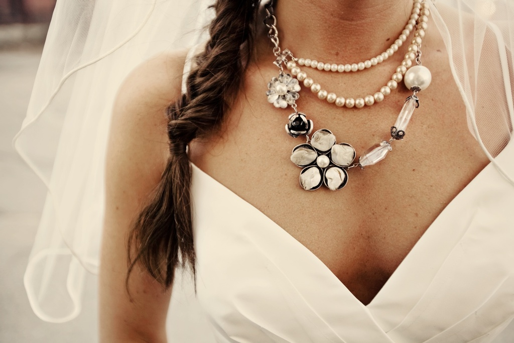 Bohemian bride wears v-neck wedding dress, statement bridal necklace