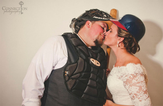 Bride and groom kiss wearing baseball gear