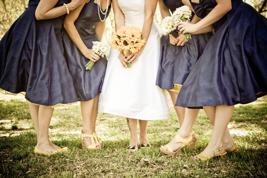 Retro Arizona bride holds sunflower bridal bouquet, poses with bridesmaids in navy blue frocks