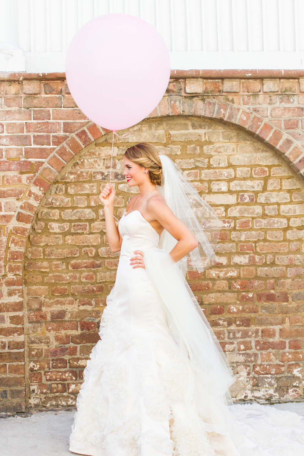 Classic-beautiful-bride-poses-with-pale-pink-balloon.full
