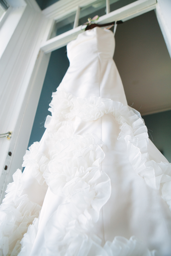 White wedding dress with cascading ruffles hangs in bridal suite