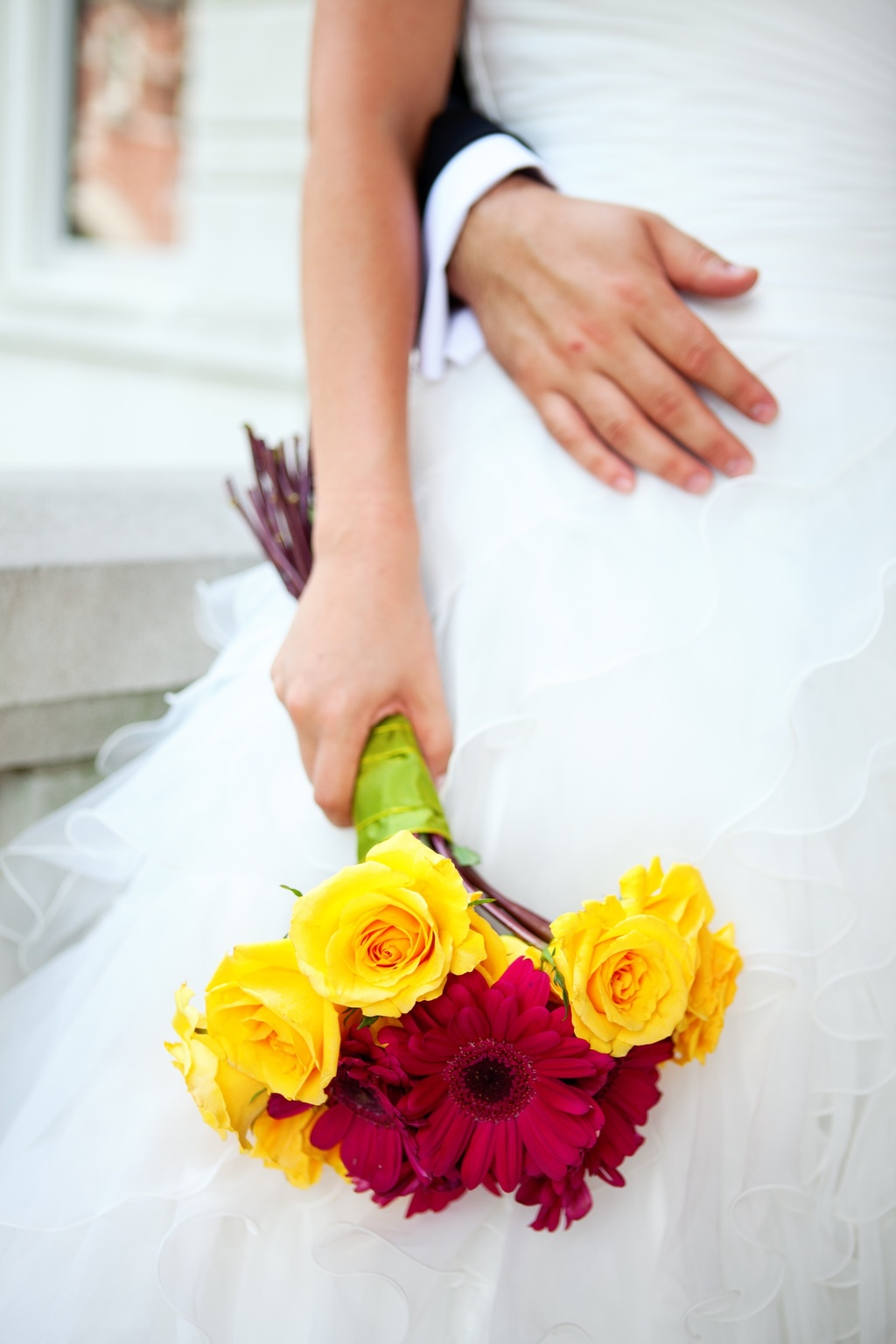 Bride holds yellow roses, red Gerbera daisies bridal bouquet