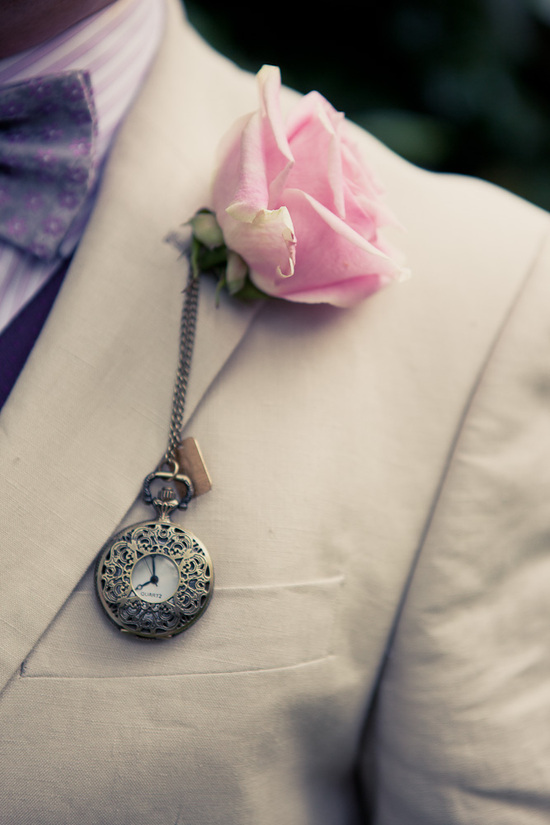 photo of Groom wears khaki tux with Alice in Wonderland inspired boutonniere