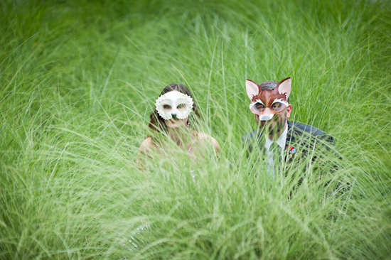 bride and groom in costume hiding in grass