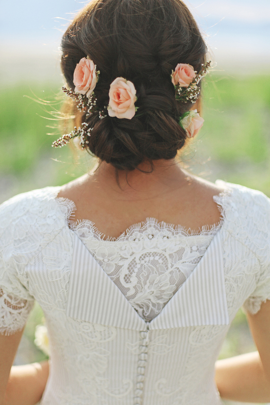 low twisted wedding updo with peach flowers