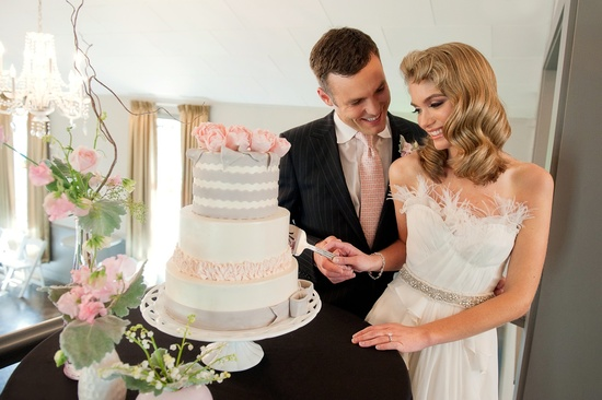 Vintage chic bride and groom cut wedding cake