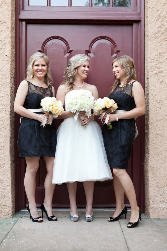 Bride in tea length wedding dress poses with bridesmaids in black