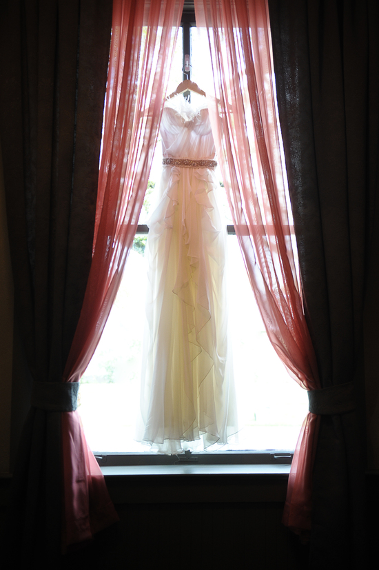 Ivory feather-adorned wedding dress hangs in window