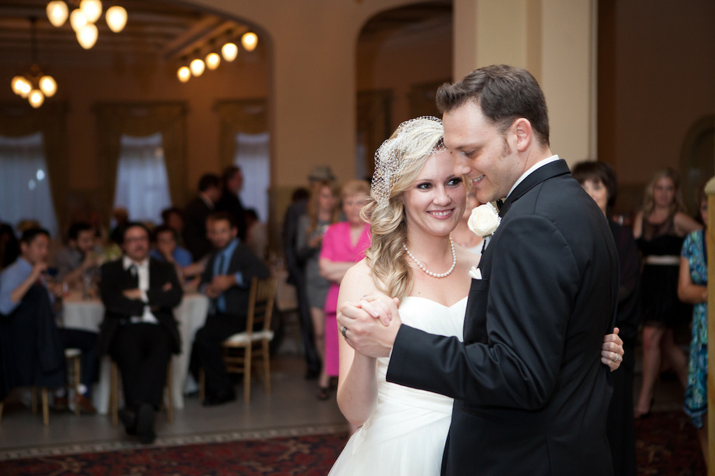 Classic-bride-and-groom-have-their-first-dance-as-guests-look-on.full