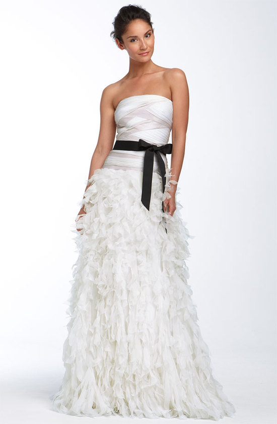 Glam strapless a-line Tadashi Shoji wedding dress with feather-embellished skirt