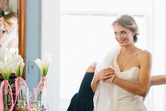 Beautiful bride smiles while getting dressed for the ceremony