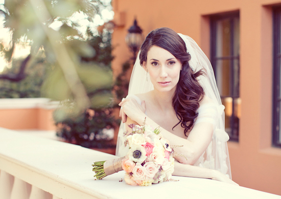 romantic bride wears side swept half up hairstyle and tulle veil