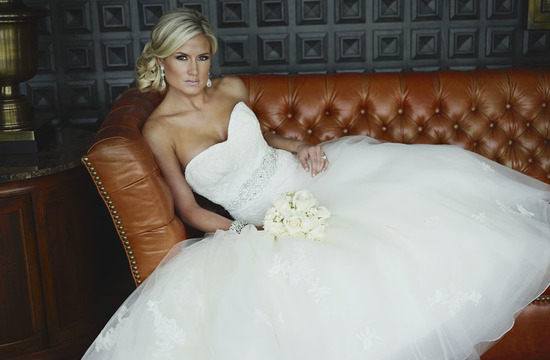 Blonde bride with golden tan poses during wedding portrait session