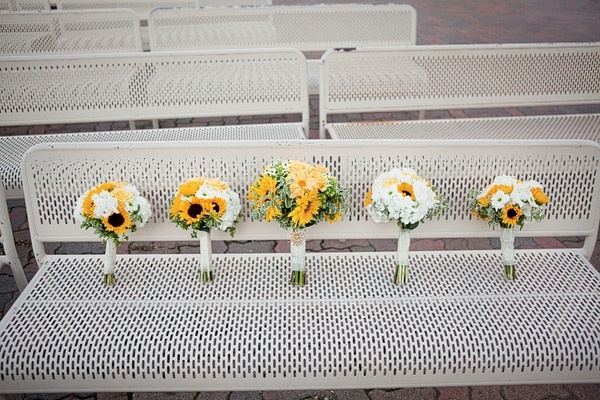 Yellow and white bride and bridesmaid bouquets photographed on park bench