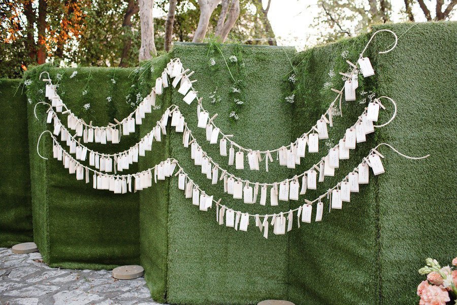 Luggage-tag-escort-cards-hanging-from-mossy-backdrop.full