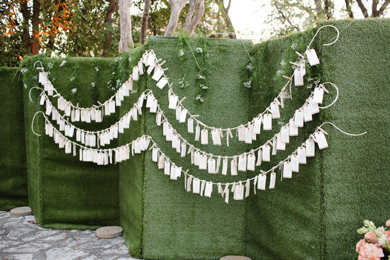 luggage tag escort cards hanging from mossy backdrop