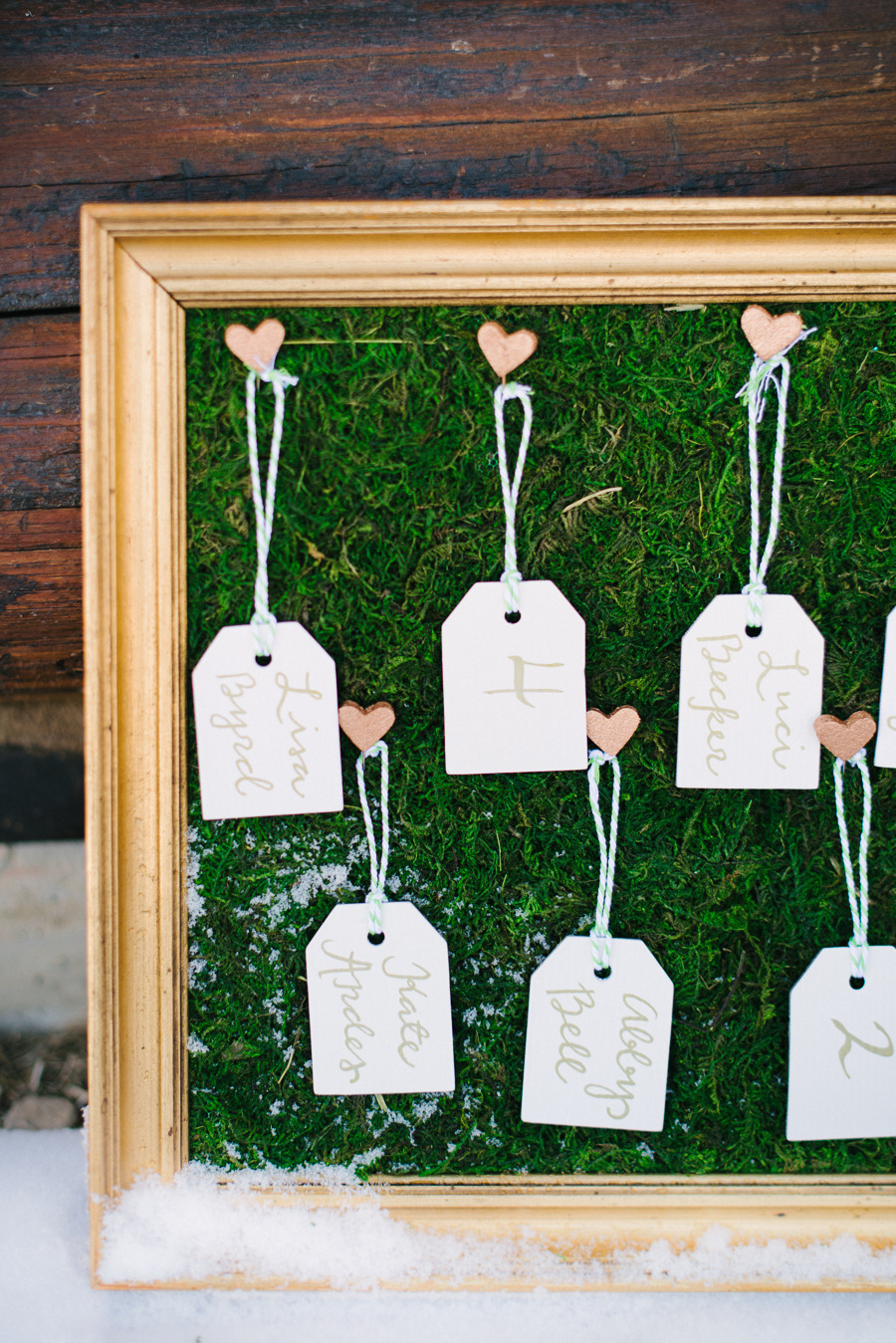 Calligraphy-escort-cards-hang-with-hearts-on-mossy-frame.full