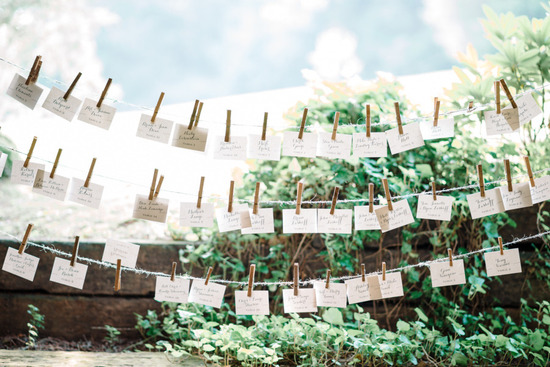 Escort cards and Polaroids hang from clothes line