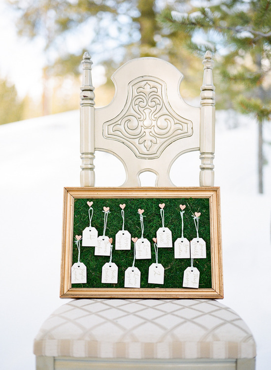 calligraphy escort cards hang with hearts on mossy frame